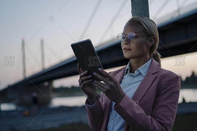 Confident female entrepreneur using digital tablet against bridge at dusk