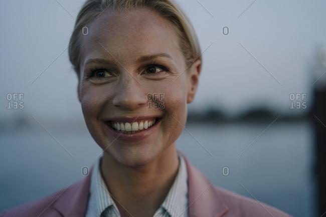 Close-up of smiling beautiful female entrepreneur looking away at dusk