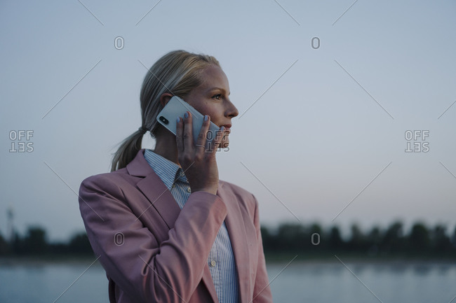 Beautiful businesswoman talking on mobile phone while looking away against sky at dusk