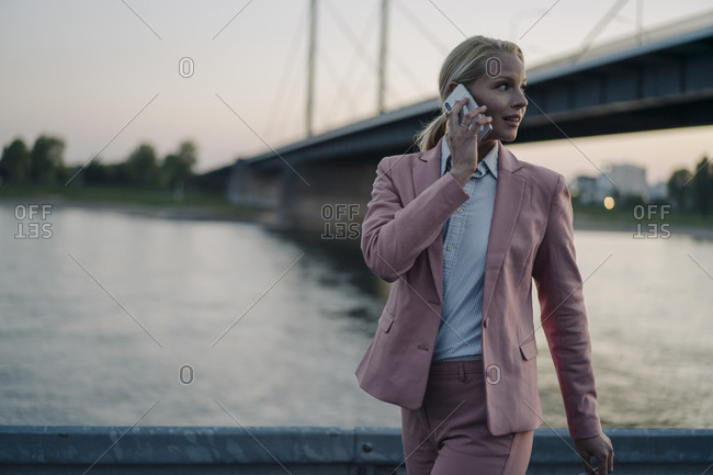 Female professional looking away while talking on smart phone against bridge at dusk
