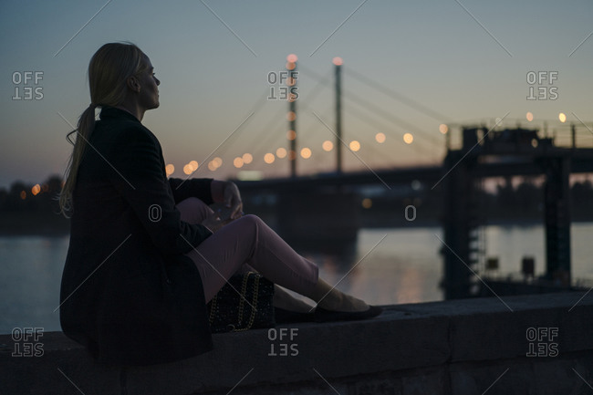 Female professional sitting on retaining wall by river at dusk