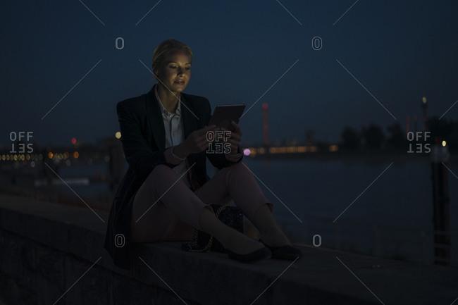 Female entrepreneur using digital tablet while sitting on retaining wall in dark against sky at dusk