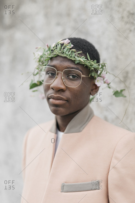 Young man wearing glasses and flower tiara on forehead