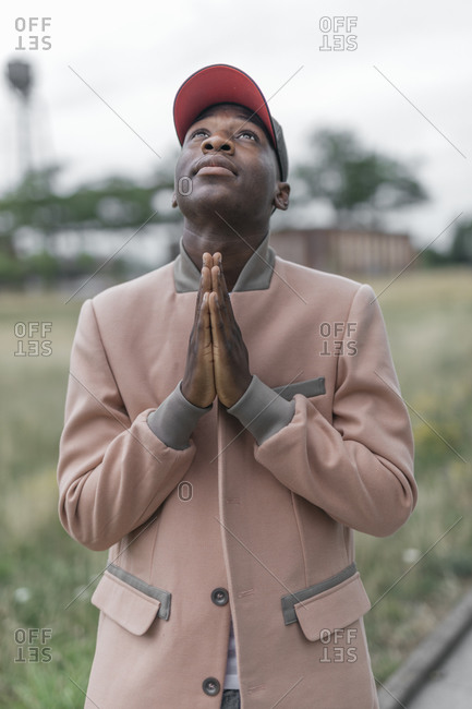 Young man praying with religious faith while standing outdoors