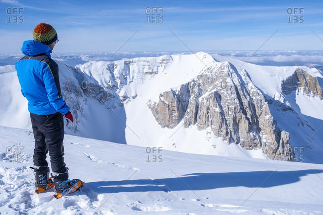Young man looking at view while standing on snowcapped mountain- Umbrian- Italy