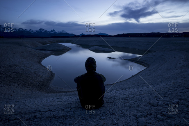 Germany- Bavaria- Silhouette of hooded man admiring Forggensee lake at dusk