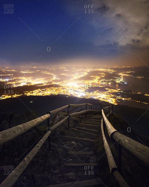 Switzerland- Canton of Lucerne- Lucerne- Steps on mountaintop of Pilatus at dusk with illuminated city in background