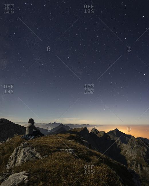 Germany- Bavaria- Man sitting at summit of Ammergau Hochplatte mountain at dusk