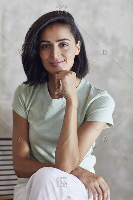 Close-up of smiling businesswoman with hand on chin sitting against wall in office