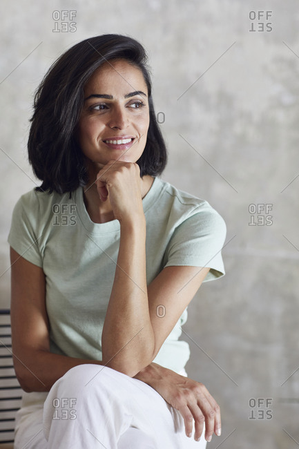 Close-up of thoughtful businesswoman with hand on chin sitting against wall in office