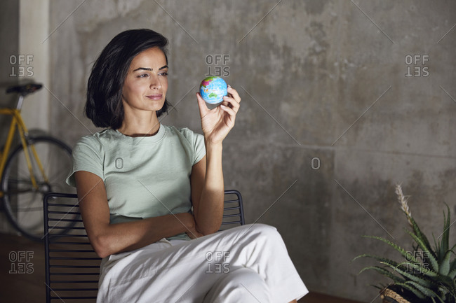 Businesswoman holding small globe while sitting on chair against wall in office