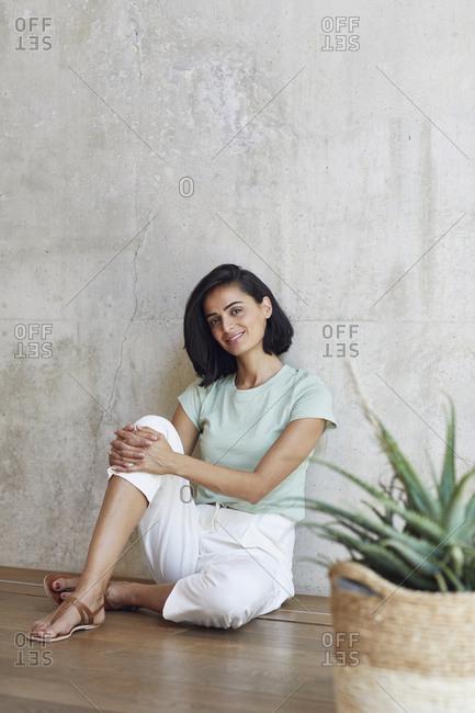Smiling female entrepreneur sitting on hardwood floor against wall in office
