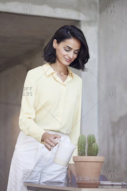 Smiling businesswoman watering cactus plant on desk in office