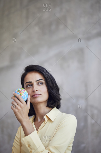 Close-up of thoughtful female entrepreneur holding small globe against wall in office