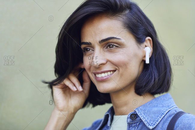 Close-up of smiling businesswoman wearing wireless headphones against wall