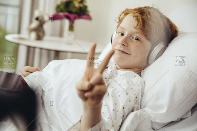 Sick boy lying in hospital making victory sign- wearing head phones
