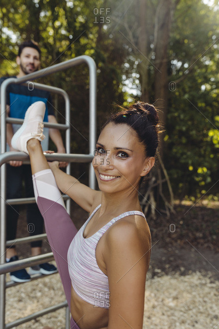 Portrait of smiling woman stretching on fitness trail