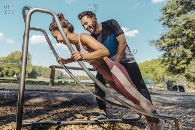 Man supporting woman doing press-ups on a fitness trail