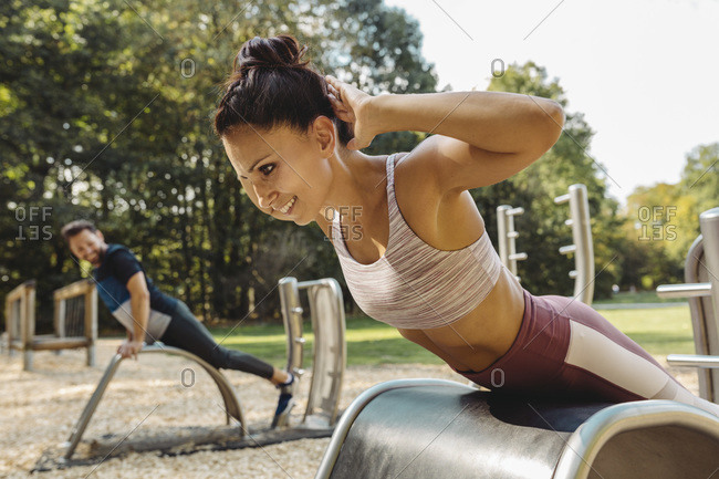 Woman doing push-ups on a fitness trail