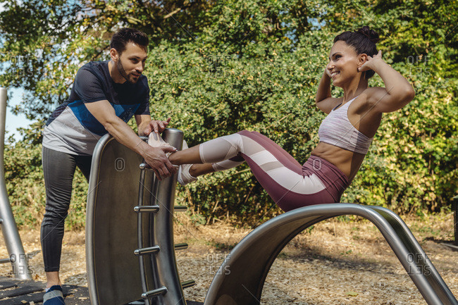Man supporting woman doing exercises on a fitness trail