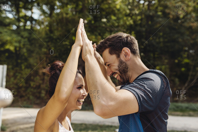 Man and woman high-fiving on a fitness trail