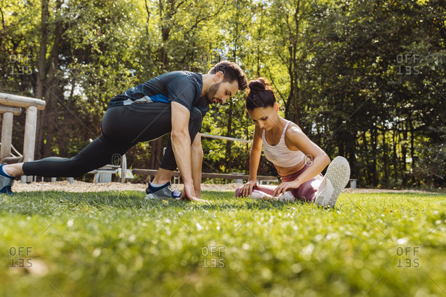 Man and woman stretching on grass near a fitness trail