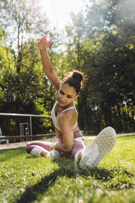 Woman stretching on grass near a fitness trail