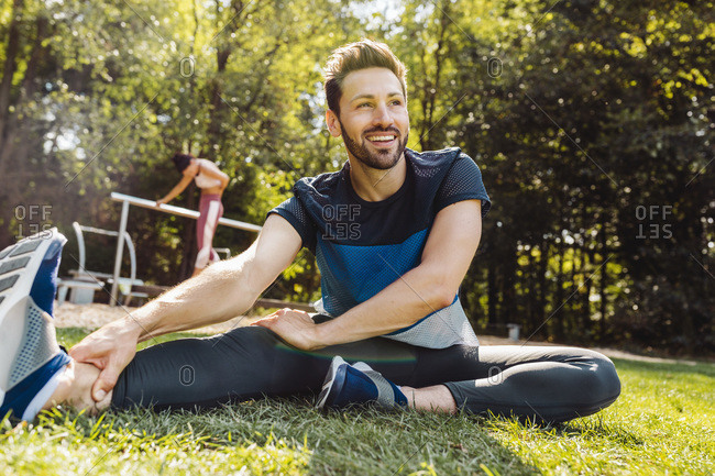 Man stretching on grass near a fitness trail