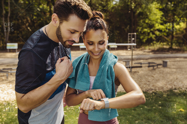 Sporty man and woman looking at a smartwatch in a park