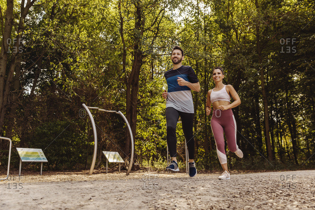 Sporty man and woman running near a fitness trail