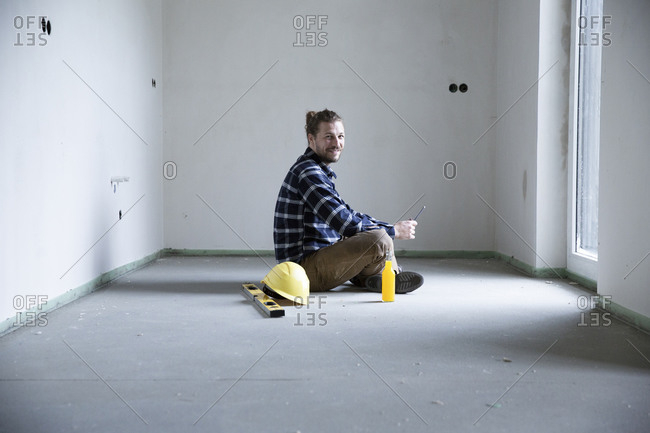 Construction worker sitting on floor in empty house at construction site