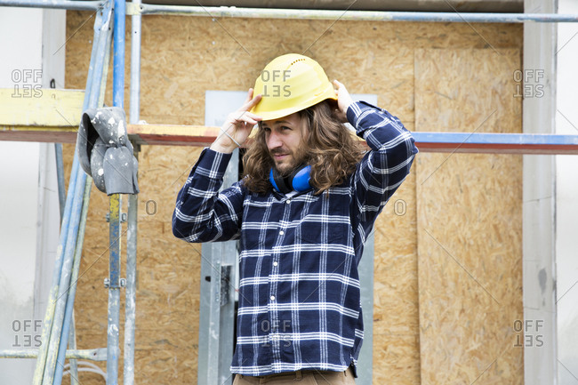 Construction worker with long hair wearing helmet while standing at construction site