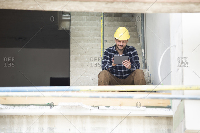 Construction worker using digital tablet while sitting on steps at construction site