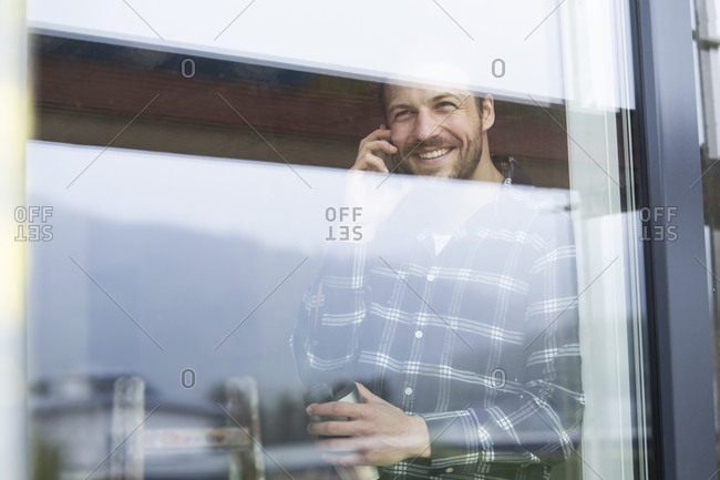 Construction worker talking over smart phone while standing by window at construction site