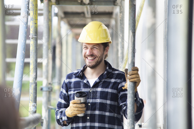 Smiling construction worker holding container standing by scaffold at construction site