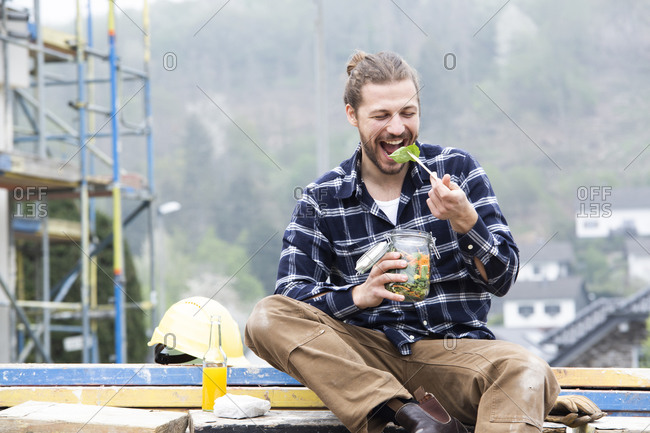 Construction worker eating salad while sitting outdoors at construction site