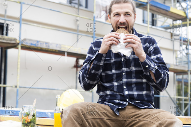 Construction worker eating bread while sitting against building at construction site