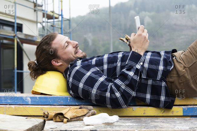 Construction worker using smart phone while eating food on wood at construction site
