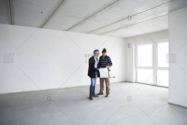 Architect and construction worker discussing blueprint while standing in empty house