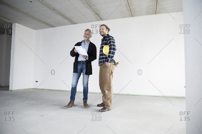Architect and construction worker looking away while standing against wall in empty house
