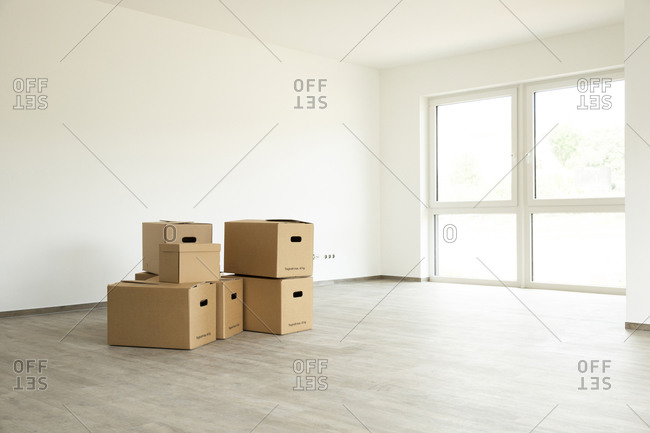 Cardboard boxes on hardwood floor against white wall in new house