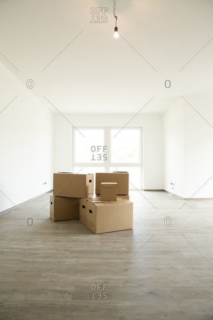 Light bulb hanging over cardboard boxes on hardwood floor in new house