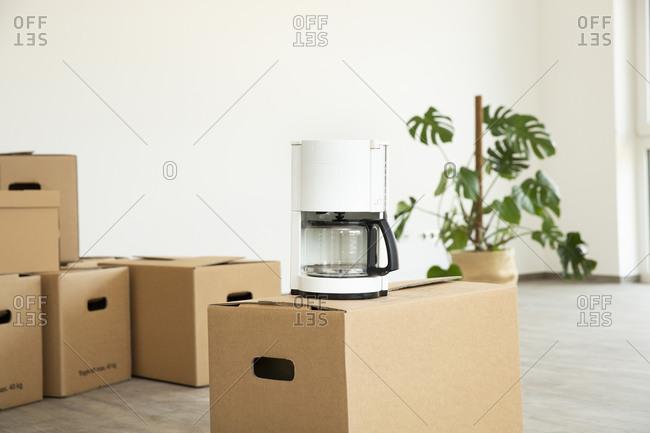 Coffee machine on cardboard box against white wall in new house