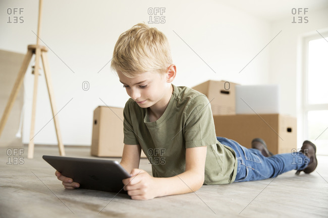 Boy with blond hair using digital tablet while lying on floor in new house
