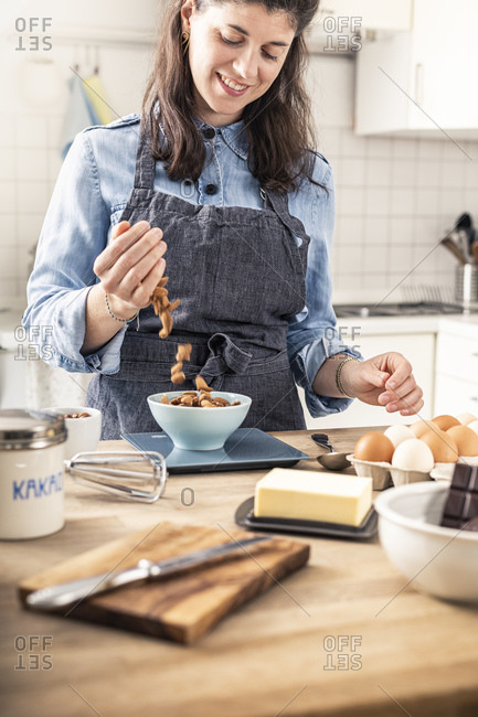 Smiling woman weighing almond on kitchen scale at home
