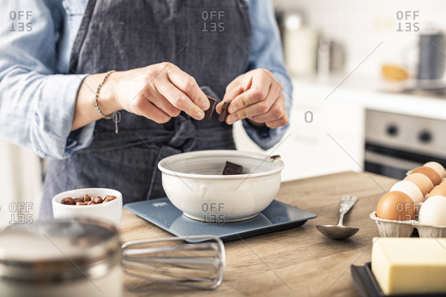 Woman weighing chocolate on kitchen scale while standing by kitchen island at home