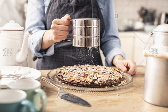 Woman sieving sugar on cake at home