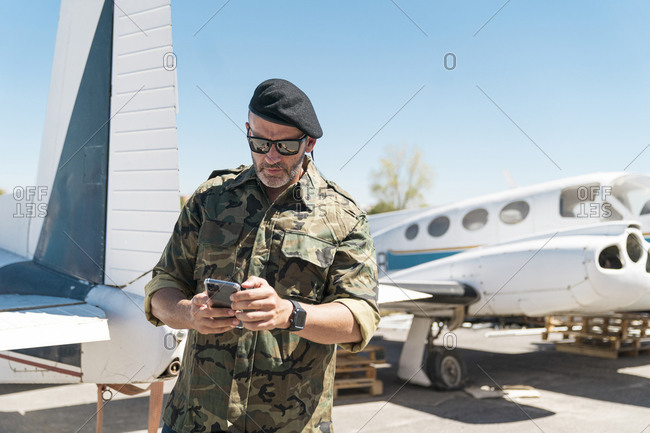Confident army soldier text messaging on smart phone while standing against airplane