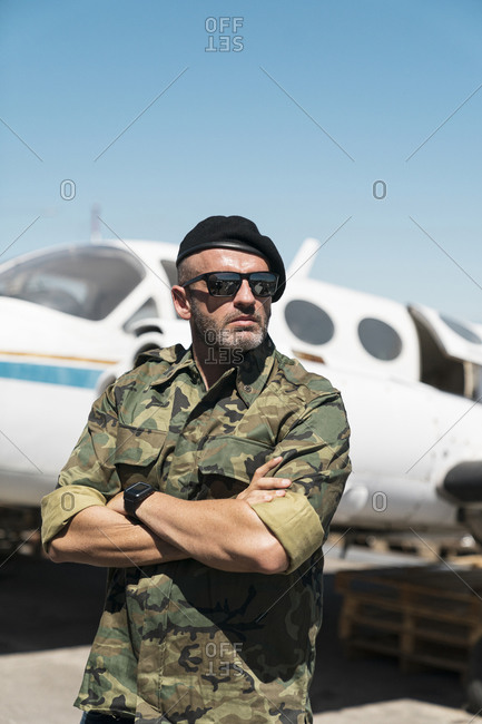 Army soldier standing with arms crossed against airplane on sunny day