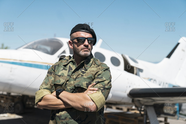 Confident army soldier standing with arms crossed against airplane on sunny day